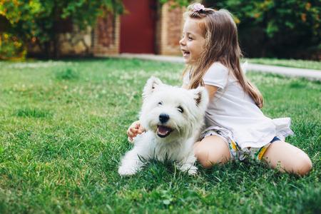 jugando: Niño que juega con el perro Inglés Terrier blanco de montaña en la hierba en el patio trasero Foto de archivo