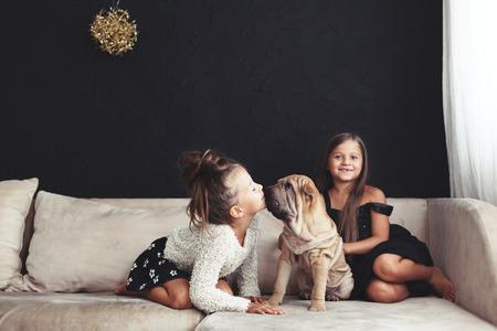Home Portrait von zwei niedlichen Kinder mit Welpen von Chinese Shar Pei Hund auf dem Sofa gegen schwarze Wand umarmen