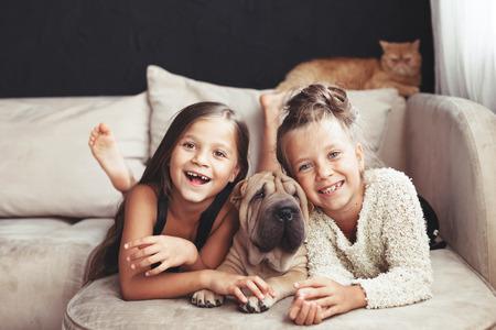 Início retrato de duas crianças bonitos que abraçam com gato do gengibre e filhote de cachorro do cão de Shar Pei no sofá contra a parede preta