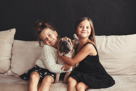 two children: Home portrait of two cute children hugging with puppy of Chinese Shar Pei dog on the sofa against black wall
