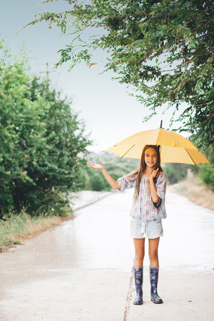 casters: Preteen child wearing rubber boots and holding umbrella walking in the rain