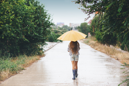 walking boots: Preteen child wearing rubber boots and holding umbrella walking in the rain