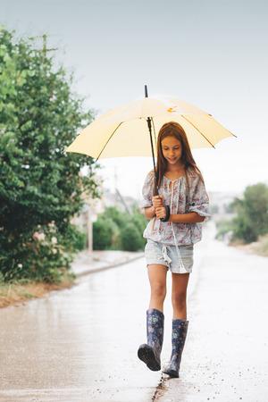 Preteen kind het dragen van rubberen laarzen en houden paraplu lopen in de regen