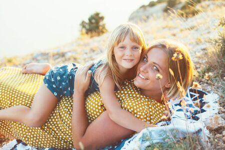 mommy: Mom playing with her child on top of the mountain in sunlight, daughter hugging mama