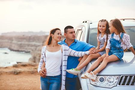 Viaje de la familia en coche por la orilla del mar en la puesta del sol, los viajes a la serie de fotos