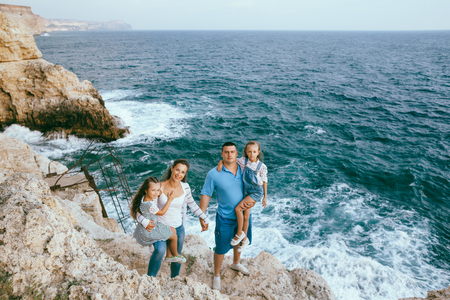 summer holidays: Family walking on the sea shore in sunset, travel photo series