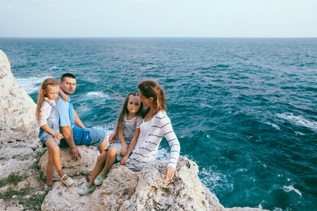 Family walking on the sea shore in sunset, travel photo series photo