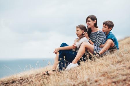 Mamma con due bambini preteen camminare all'aperto, fresco clima autunnale