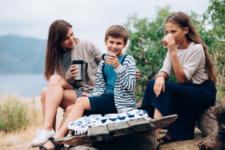 madre e hija adolescente: Madre con dos niños preadolescentes que tienen comida campestre al aire libre, el clima fresco de otoño