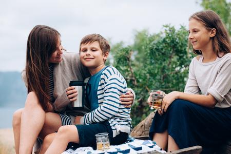 madre e hijo: Madre con dos niños preadolescentes que tienen comida campestre al aire libre, el clima fresco de otoño