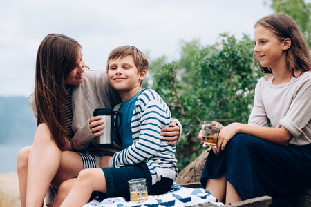 mommy: Mom with two preteen children having picnic outdoor, cool autumn weather