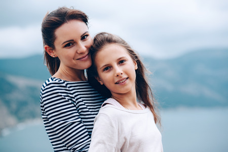 mama e hija: Mom and her teenage daughter hugging and smiling together over blue sea view Foto de archivo