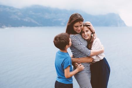 madre e hijo: Madre con dos niños preadolescentes caminando al aire libre, clima fresco de otoño