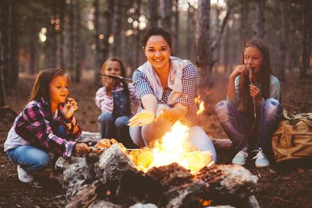 Groupe d'enfants avec maman assis près du feu et de boire du thé dans la forêt d'automne, la randonnée le week-end Banque d'images