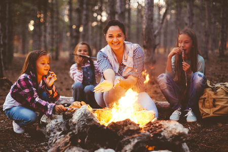 Gruppo di bambini con la mamma seduta accanto al fuoco e bere il tè in autunno foresta, escursioni nel fine settimana Archivio Fotografico