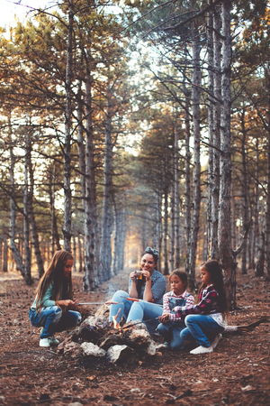 forest tea: Group of kids with mom sitting by the fire and drinking tea in autumn forest, hike at weekend