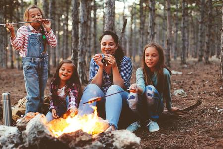 mama e hija: Grupo de cabritos con la madre se sienta junto al fuego y beber el té en otoño de bosque, caminar en fin de semana Foto de archivo