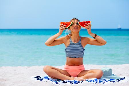 夏の晴れた日のビーチでスイカを食べる女