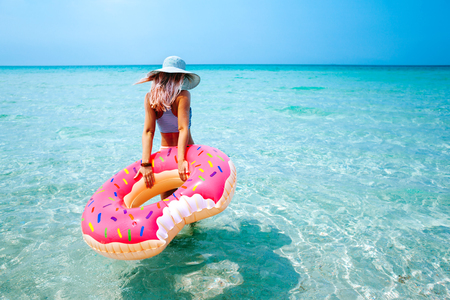 Donna di nuoto con la ciambella gonfiabile sulla spiaggia di giornata di sole estivo Archivio Fotografico