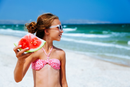 Child eating watermelon on the beach in summer sunny day