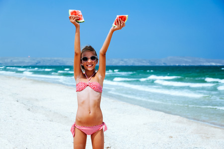 tween: Child eating watermelon on the beach in summer sunny day