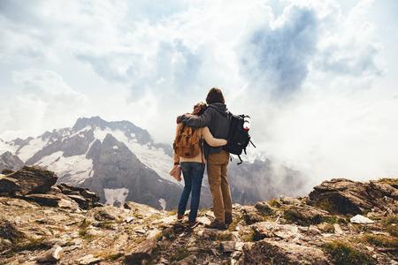 Muž a žena stojící a objímání na vrcholu hory, podzimní výlet s batohy, výhled na alpské