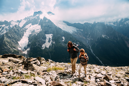 Father with child walking on the top of the mountain, winter hike with backpacks, alpine view