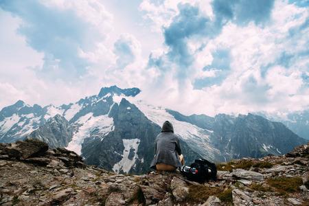 Hombre solo con mochila sentado en la cima de la montaña y mirando la belleza del paisaje