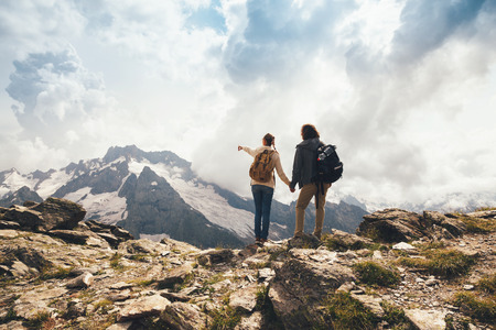 top mountain: Man and woman standing and hugging on the top of the mountain, autumn hike with backpacks, alpine view Stock Photo