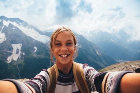 chica pre adolescente que toma la foto autofoto en la cima de la montaña, caminata de otoño con mochilas, vista alpino Foto de archivo