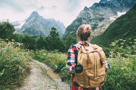 Hiker with backpack looking at mountains, alpine view Stock Photo