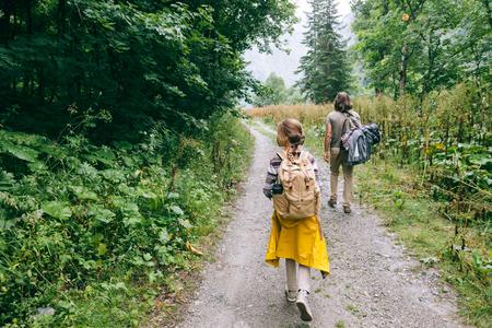 Wanderer mit Rucksäcken im Wald spazieren, Vater mit Kind