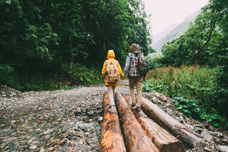 rain weather: Hikers with backpacks walking in the forest, father with child, rain weather