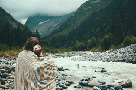 blanket: Man and woman wrapped in warm blanket outdoor, hiking in mountains, bad cold weather with fog