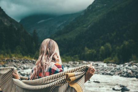 Girl wrapping in warm blanket outdoor, hiking in mountains, bad cold weather with fog Banco de Imagens