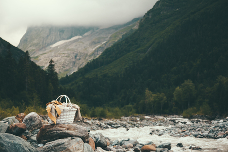 cold season: Closeup photo of wicker basket with blanket over mountains view, picnic in cold season Stock Photo