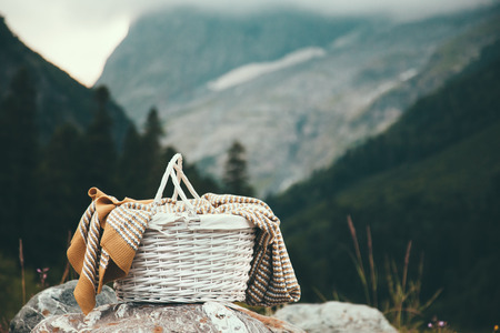 blanket: Closeup photo of wicker basket with blanket over mountains view, picnic in cold season Stock Photo
