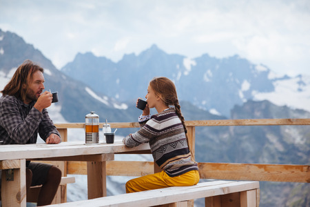dombay: Father with daughter drinking warm tea in the rustick wooden outdoor cafe on mountain, alpine view, snow on hills. Winter weekend. Dombay, Karachay-Cherkessia, Caucasus, Russia.