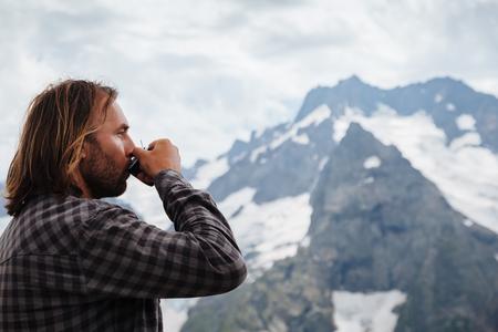 dombay: Man drinking hot tea on mountain, alpine view, snow on hills. Dombay, Karachay-Cherkessia, Caucasus, Russia.