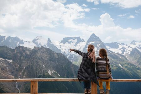 dombay: Mom with daughter relaxing in the rustick wooden terrace on mountain, alpine view, snow on hills. Dombay, Karachay-Cherkessia, Caucasus, Russia.
