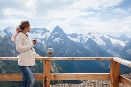 dombay: Woman drinking warm tea in the rustick wooden terrace on mountain, alpine view, snow on hills. Dombay, Karachay-Cherkessia, Caucasus, Russia. Stock Photo