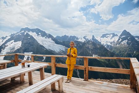 dombay: Child drinking warm tea in the rustick wooden outdoor cafe on mountain, alpine view, snow on hills. Dombay, Karachay-Cherkessia, Caucasus, Russia.