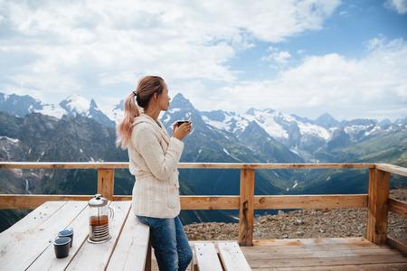 dombay: Woman drinking warm tea in the rustick wooden outdoor cafe on mountain, alpine view, snow on hills. Dombay, Karachay-Cherkessia, Caucasus, Russia.