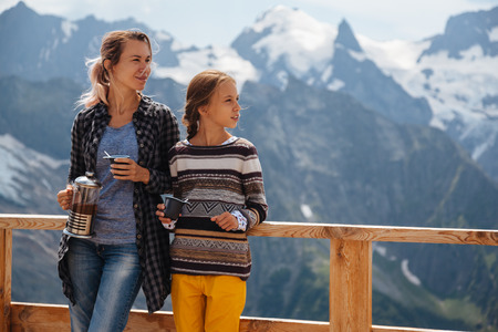 dombay: Mom with daughter drinking warm tea in the rustick wooden terrace on mountain, alpine view, snow on hills. Winter weekend. Dombay, Karachay-Cherkessia, Caucasus, Russia. Stock Photo