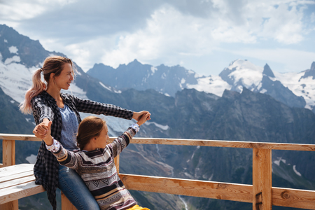 dombay: Mom with daughter relaxing in the rustick wooden terrace on mountain, alpine view, snow on hills. Winter weekends. Dombay, Karachay-Cherkessia, Caucasus, Russia.