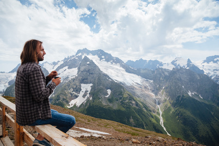 Man drinking hot tea on mountain, alpine view, snow on hills. Dombay, Karachay-Cherkessia, Caucasus, Russia.