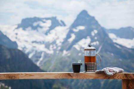 dombay: Tea on terrace on the mountain, alpine view, snow on hills. Dombay, Karachay-Cherkessia, Caucasus, Russia. Stock Photo