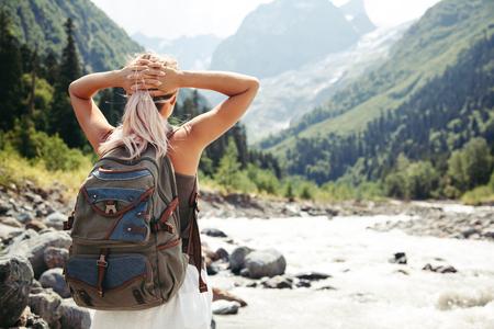 背包客行走在河邊。旅行者站立,看著美麗的景色。