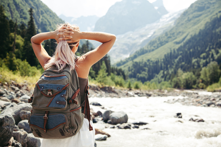 Backpacker lopen door de rivier. Traveler staan en kijken naar een prachtig uitzicht. Stockfoto