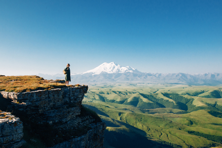 top of the world: Traveler standing on top of Bermamyt plateau and looking on Elbrus mountain. Karachay-Cherkessia, Caucasus, Russia. Stock Photo